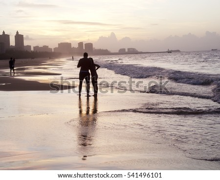 Romantic couple walking along the beach at sunset. Journey. vacation. tourism.