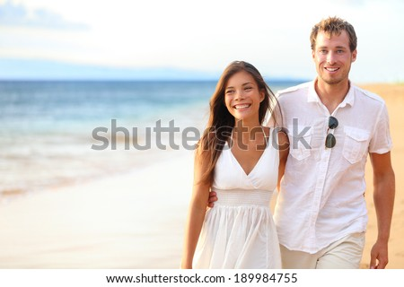 Romantic couple walking on beach on honeymoon travel vacation summer holidays romance. Young happy lovers, Asian woman and Caucasian man holding hands embracing outdoors. - stock photo