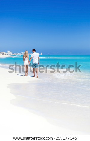 Romantic couple walking on perfect beach with turquoise sea, enjoying life and each other at honeymoon vacation. Back view