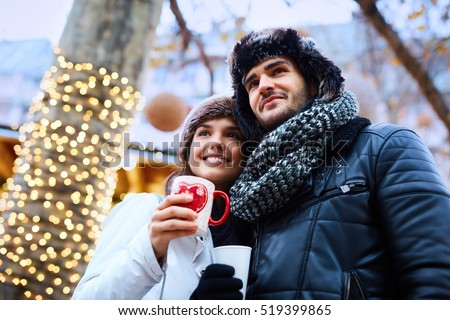 Romantic couple walking on street at christmas time, drinking hot drinks, smiling happy.