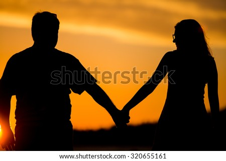 Romantic couple walking on the beach at colorful sunset on background - stock photo