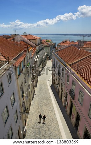 Romantic couple walking on the narrow street of old Europe. Lisbon, capital of Portugal. - stock photo