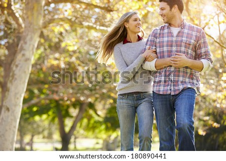 Romantic Couple Walking Through Autumn Woodland - stock photo