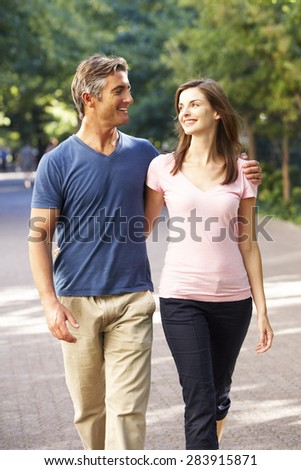 Romantic Couple Walking Through Summer Park - stock photo