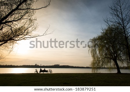 Romantic couple watching the sun goes down - stock photo