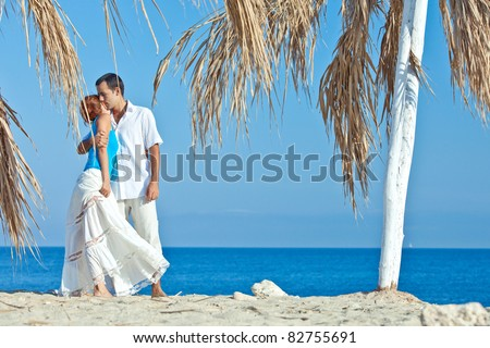 romantic couple wearing hats on the beach - stock photo