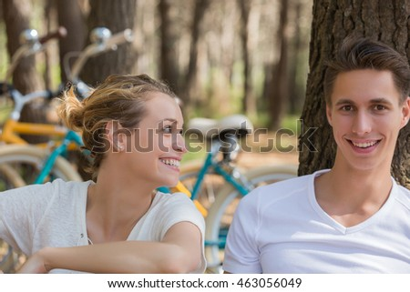 romantic couple with bicycle spending time in forest