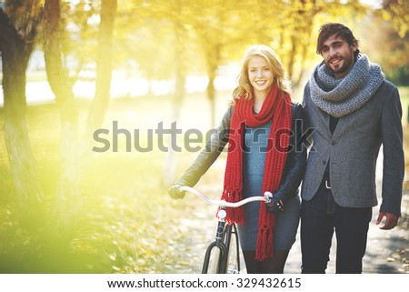 Romantic couple with bicycle spending weekend in autumn park - stock photo