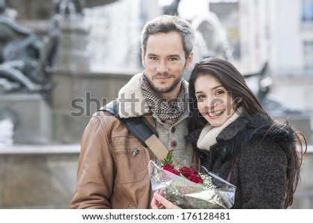 romantic couple with flowers bouquet with fountain in background