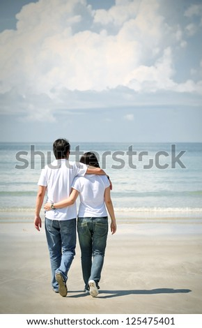 romantic couples walking together on the beach - stock photo