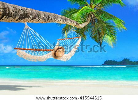 Romantic cozy hammock with straw hat in the shadow of coconut palm tree at tropical paradise ocean beach in bright sunny summer day - vacation background - stock photo