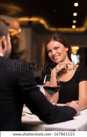 Romantic date at the restaurant. Beautiful young couple talking to each other and smiling while spending time at the restaurant - stock photo