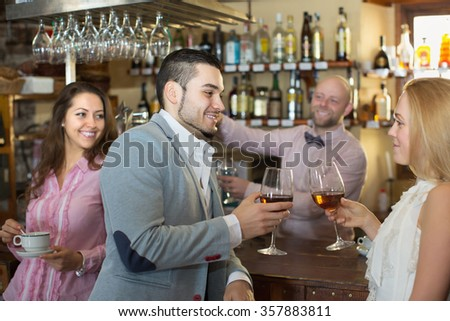 Romantic date of young couple drinking wine at bar and smiling. Focus on young man - stock photo