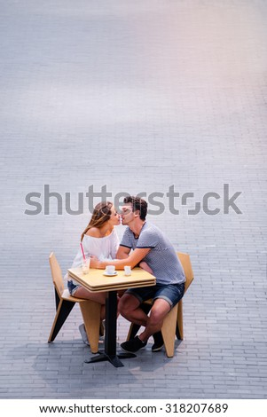Romantic date. Pretty young loving couple sitting in sidewalk cafe together.