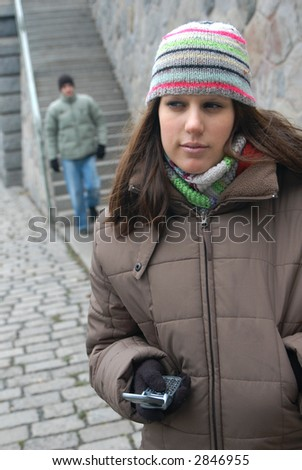 Romantic date. Young girl with a cell phone waiting for a boyfriend going down to the steps