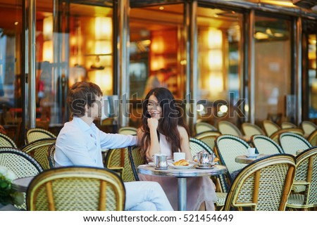 Romantic dating couple drinking coffee and eating traditional French croissants in cafe. Paris, France