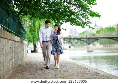 Romantic dating couple is walking by the water in Paris - stock photo