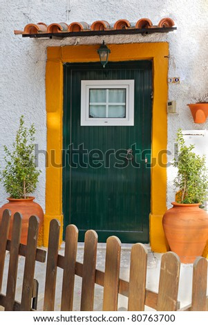 romantic, decorated entrance door Mediterranean style behind a picket fence in Portugal - stock photo