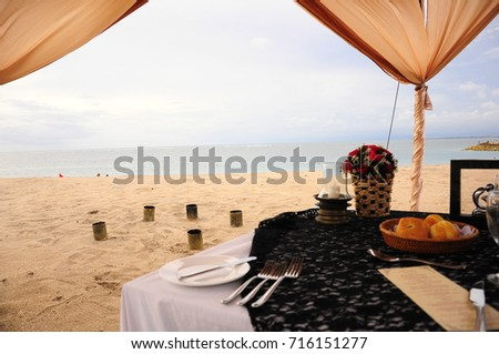 https://thumb7.shutterstock.com/display_pic_with_logo/167494286/716151277/stock-photo-romantic-dinner-by-bali-s-seaside-716151277.jpg