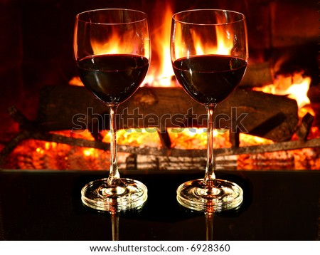 Romantic dinner for two, two glasses of red wine and fireplace. - stock photo