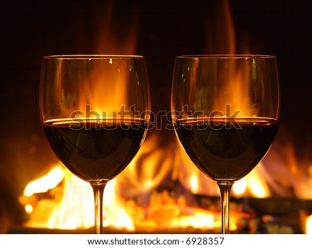Romantic dinner for two, two glasses of red wine (close up) and fireplace. - stock photo