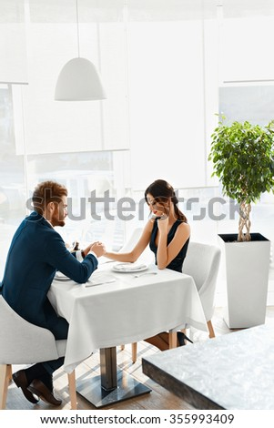 Romantic Dinner. Happy Lovely Couple Celebrating Anniversary Or Valentine's Day Together In Luxury Fancy Gourmet Restaurant. Love, Romance, Relationships Concept.