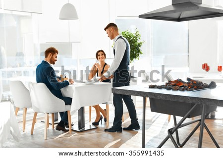 Romantic Dinner. Happy Smiling Couple In Love Reading Menu And Ordering Food To Waiter In Luxury Gourmet Restaurant. People Celebrating Anniversary Or Valentine's Day. Romance, Relationships Concept. - stock photo