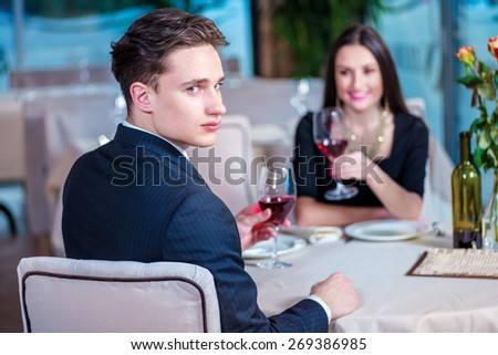 Romantic dinner in the restaurant. Young couple sitting at a table at each other and smiling lovingly at the restaurant while toasting with wine. - stock photo