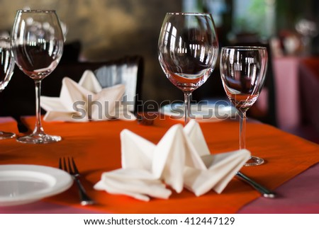 Romantic dinner interior, hotel service concept. Served table in a banquet hall. White plate knife fork and wine glasses on red napkin. Soft focus, shallow depth of field - stock photo