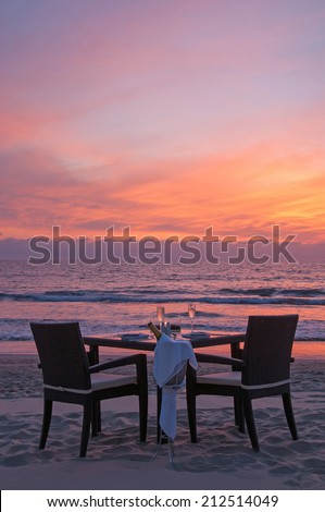 romantic dinner on the beach with sunset - stock photo