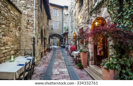 Romantic dinner place in a beautiful alley in the ancient town of Assisi, Umbria, Italy - stock photo