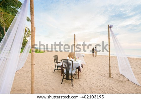 Romantic dinner setting on the beach at sunset. - stock photo