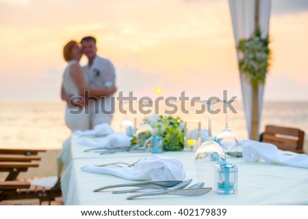 Romantic dinner setting on the beach at sunset with couples background - stock photo