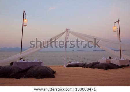 Romantic dinner setting on tropical beach at sunset - stock photo