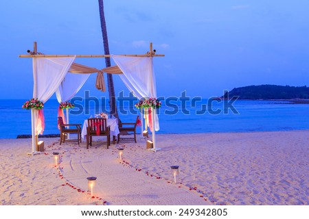 romantic dinner setup on the beach while twilight - stock photo