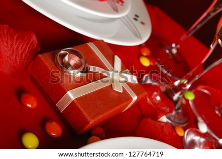 romantic dinner table and wedding rings on red background - stock photo