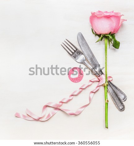 Romantic dinner table place setting with fork, knife , pink rose and heart on  white wooden background, top view. Love symbol. Valentine Day or Birthday concept. - stock photo
