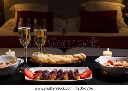 romantic dinner with champagne in the bedroom. Low key - stock photo