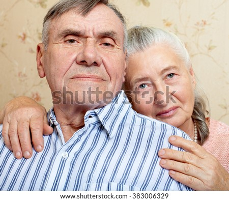 Romantic elderly man and woman sitting close together on a sofa in their living room in a loving embrace  looking at the camera - stock photo
