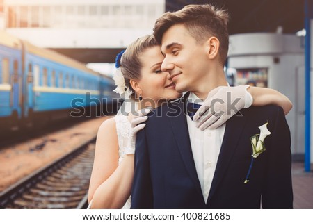 Romantic embrace of newlyweds. Groom and bride are embracing. Couple are smiling, they are happy. Bride put her hands on the shoulders of groom. Newlyweds in love. There is train in the background.  - stock photo