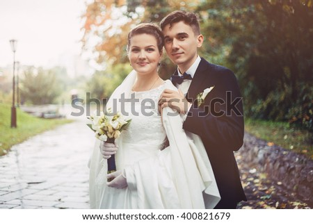 Romantic embrace of newlyweds. The groom is embracing bride from behind. They are walking in park. Bride is smiling, she happy. Newlyweds in love. They became husband and wife this day. - stock photo