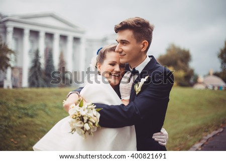 Romantic embrace of newlyweds. The groom is embracing bride from behind. They are walking in park at their wedding day. Couple are smiling, they are happy. Newlyweds in love.  - stock photo