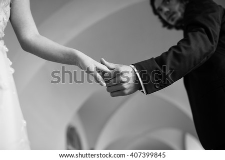 Romantic emotional newlyweds holding hands under building archway closeup