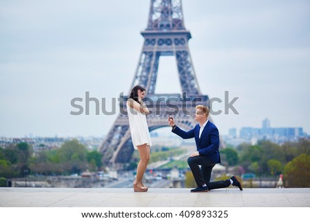 Romantic engagement in Paris, man proposing to his beautiful girlfriend near the Eiffel tower. Surprise proposal or elopement concept - stock photo