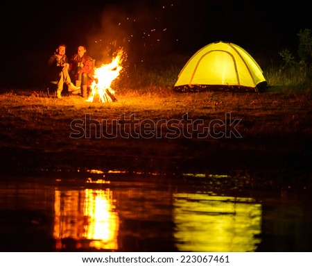 Romantic evening. A charming couple, camping, sitting around the campfire - stock photo