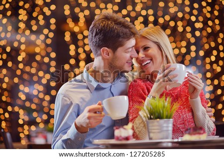 romantic evening date in restaurant  happy young couple with wine glass tea and cake - stock photo