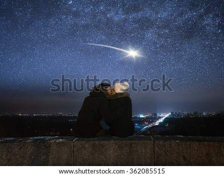 Romantic evening. Loving couple kissing. Night in city. Meteor in night sky