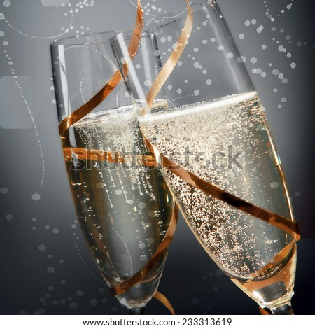 Romantic flutes of sparkling golden champagne with effervescent bubbles wrapped in golden ribbon to celebrate a wedding, Valentines, New Year or anniversary, close up detail on grey - stock photo