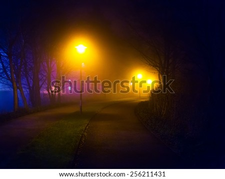 Romantic foggy night walk in a park with street lights (diffused, toned) - stock photo