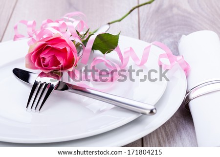 Romantic formal elegant table setting with a single pink rose and decorative ribbon for a sweetheart on Valentines Day - stock photo